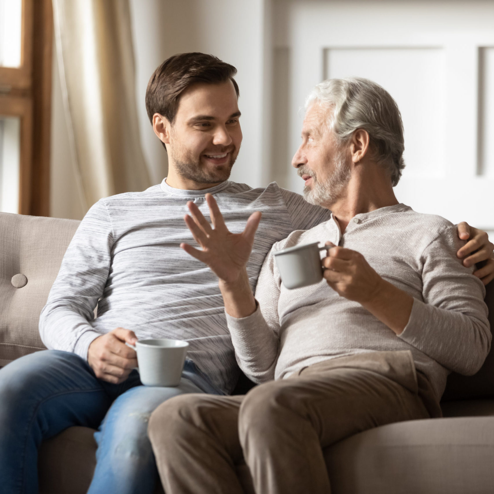 Happy mature father and adult son drinking tea together, chatting, enjoying pleasant conversation, leisure time, sitting on cozy couch at home, smiling grandfather and grandson holding cups